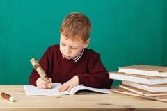 Piccole note sorridenti di scrittura dello scolaro nella classe contro il wa verde Fotografia Stock Libera da Diritti