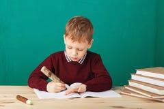Piccole note sorridenti di scrittura dello scolaro nella classe contro il wa verde Fotografie Stock Libere da Diritti
