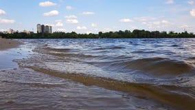 Piccole onde che lavano su una riva del fiume con la sabbia marrone chiaro in un giorno soleggiato stock footage