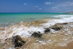 Piccole onde del mare che schiacciano sulle rocce nere alla spiaggia sabbiosa, beautifu fotografie stock libere da diritti