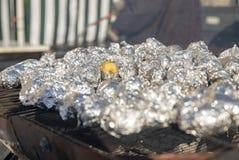 Piccole patate in stagnola sulla griglia fotografia stock libera da diritti