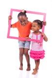 Piccole ragazze afroamericane che tengono una cornice Fotografia Stock
