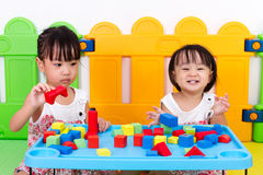 Piccole ragazze cinesi asiatiche che giocano i blocchi di legno Fotografia Stock