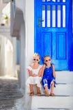 Piccole ragazze felici in vestiti alla via del villaggio tradizionale greco tipico con le pareti bianche e le porte variopinte so Immagini Stock
