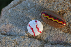 Piccole rocce dipinte del hot dog e di baseball Fotografia Stock