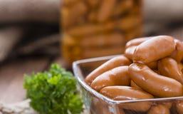 Piccole salsiccie su legno Immagini Stock