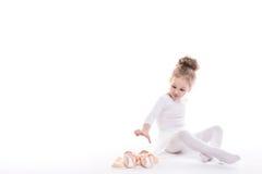 Piccole scarpe di balletto e della ballerina su un fondo bianco fotografia stock