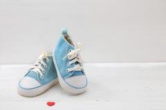 Piccole scarpe di bambino su fondo di legno bianco Immagine Stock
