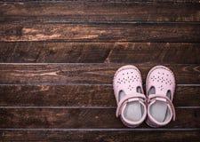 Piccole scarpe su un pavimento di legno scuro Paia delle scarpe della neonata A Fotografia Stock