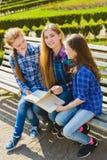 Piccole scolare graziose che leggono un libro e che si siedono sul banco all'aperto Immagini Stock