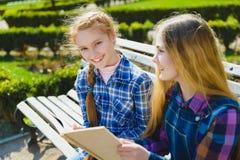 Piccole scolare graziose che leggono un libro e che si siedono sul banco all'aperto Fotografia Stock