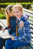 Piccole scolare graziose che leggono un libro e che si siedono sul banco all'aperto Immagine Stock