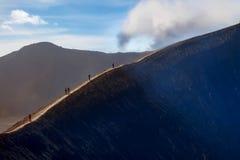 Piccole siluette della gente sull'orlo del cratere del vulcano attivo Bromo L'potenza della natura l'indonesia fotografia stock libera da diritti
