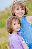 Piccole sorelle felici sulla priorità bassa verde del prato Immagini Stock