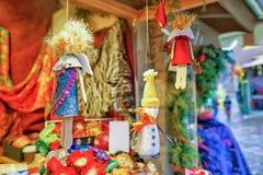 Piccole statue fatte a mano che appendono sull'esposizione al mercato di Natale di Riga Fotografia Stock