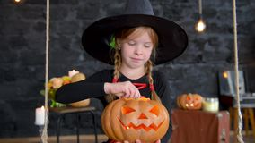 Piccole streghe di Childs su Halloween su un fondo nero, zucca della tenuta della ragazza con una candela bruciante stock footage