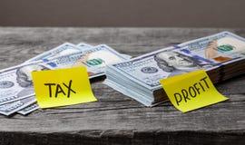 Piccole tasse sui grandi profitti, concetto Autoadesivi dell'ufficio sulle banconote in dollari sulla tavola di legno fotografie stock