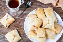 Piccole torte di mele o calzoni alle mele con cannella su un piatto bianco con la tazza di tè e le mele mature nel fondo Fotografia Stock
