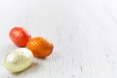 Piccole uova di Pasqua del cioccolato su un fondo bianco rustico Immagine Stock