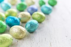 Piccole uova di Pasqua del cioccolato su un fondo bianco rustico Fotografia Stock Libera da Diritti