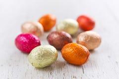 Piccole uova di Pasqua del cioccolato su un fondo bianco rustico Fotografie Stock Libere da Diritti