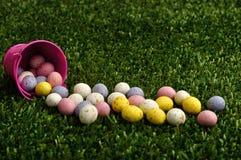 Piccole uova di Pasqua macchiate che si rovesciano da un secchio rosa Fotografia Stock