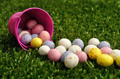 Piccole uova di Pasqua macchiate che si rovesciano da un secchio rosa Immagini Stock Libere da Diritti