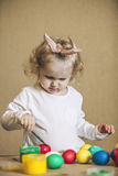Piccole uova di Pasqua sveglie di colore del bambino sulla tavola a colori, felici Fotografie Stock Libere da Diritti