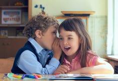 Piccoli allievi che bisbigliano i segreti durante la classe alla scuola elementare Fotografia Stock