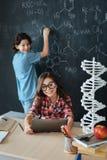 Piccoli allievi felici che godono della classe di chimica alla scuola Fotografia Stock Libera da Diritti