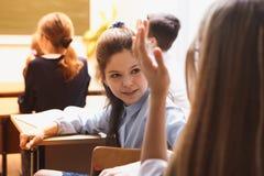 Piccoli allievi nella lezione studenti della scuola elementare del ` s La ragazza scrive diligente, Su uno scrittorio della scuol Immagine Stock Libera da Diritti