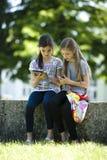 Piccoli amici con il ridurre in pani del PC ed il telefono mobile Fotografia Stock