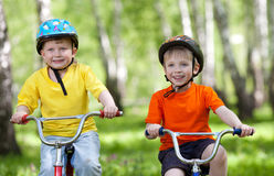 Piccoli bambini che guidano le loro bici Immagine Stock