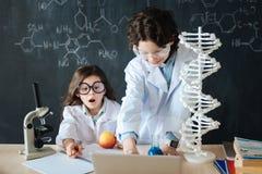 Piccoli bambini enormi che studiano microbiologia alla scuola Fotografia Stock