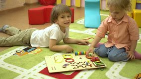 Piccoli bambini prescolari che giocano con i giocattoli educativi nell'asilo stock footage