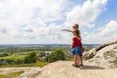 Piccoli bambini ragazzo e ragazza che stanno sulla roccia e sul looki della montagna fotografie stock