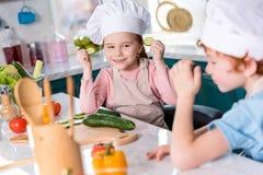 piccoli bambini svegli in cappelli del cuoco unico divertendosi mentre cucinando insieme immagini stock libere da diritti