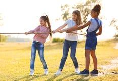 Piccoli bambini svegli che giocano con la corda all'aperto immagine stock libera da diritti