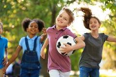 Piccoli bambini svegli che giocano con la palla all'aperto fotografia stock libera da diritti