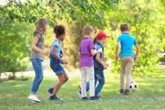 Piccoli bambini svegli che giocano con la palla all'aperto fotografia stock