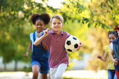 Piccoli bambini svegli che giocano con la palla all'aperto immagini stock