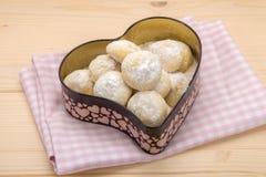 Piccoli biscotti in zucchero in polvere in un contenitore di latta nella forma del cuore sulla c fotografia stock