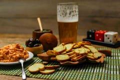 Piccoli chip del pane tostato o di Bruschetta di melba sulla tavola di legno con birra e salse fotografia stock libera da diritti