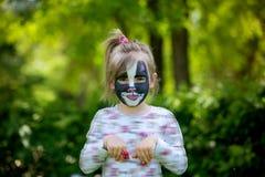 Piccoli cinque anni svegli della ragazza, facendo il suo dipingere fronte come kitt Fotografie Stock