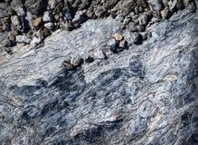 Piccoli ciottoli su una mica della roccia Immagini Stock