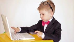 Piccoli computer portatile di uso del ragazzo del bambino di affari e carta di credito svegli stock footage