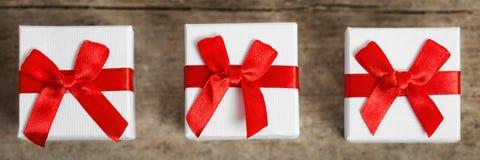 Piccoli contenitori di regali con i nastri rossi sulla tavola di legno, panorama Immagine Stock Libera da Diritti