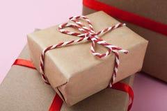 Piccoli contenitori di regalo fatti a mano con un nastro rosso su un fondo rosa fotografia stock libera da diritti