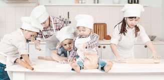 Piccoli cuochi unici felici che preparano pasta nella cucina Fotografia Stock