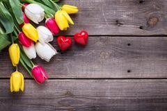 Piccoli cuori decorativi e tulipani luminosi della molla Fotografie Stock
